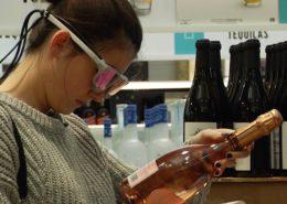 Participante portant des lunettes oculométriques et regardant une bouteille dans une succursale de la SAQ