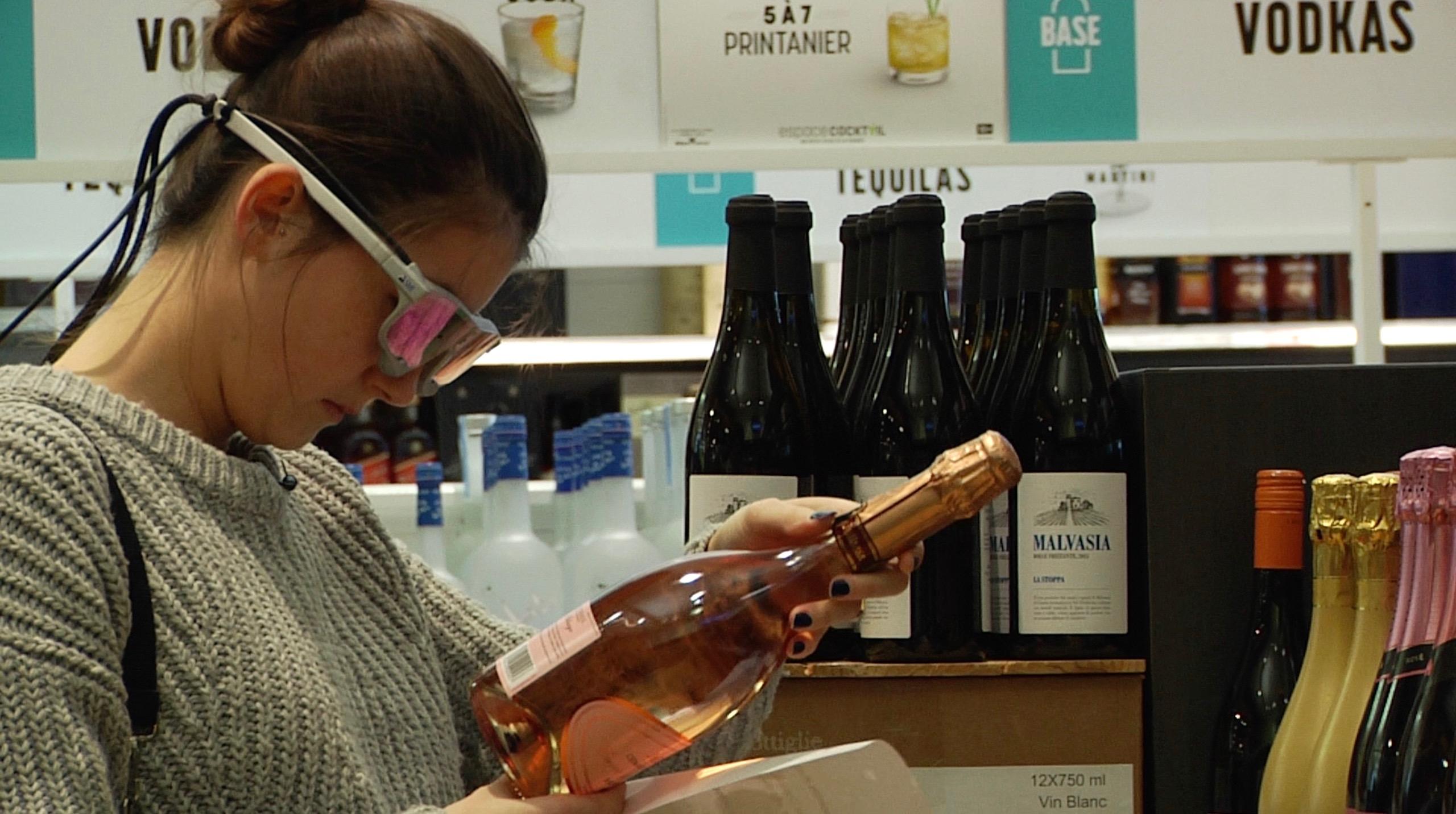 Participante avec lunettes oculométriques regardant une bouteille à la SAQ